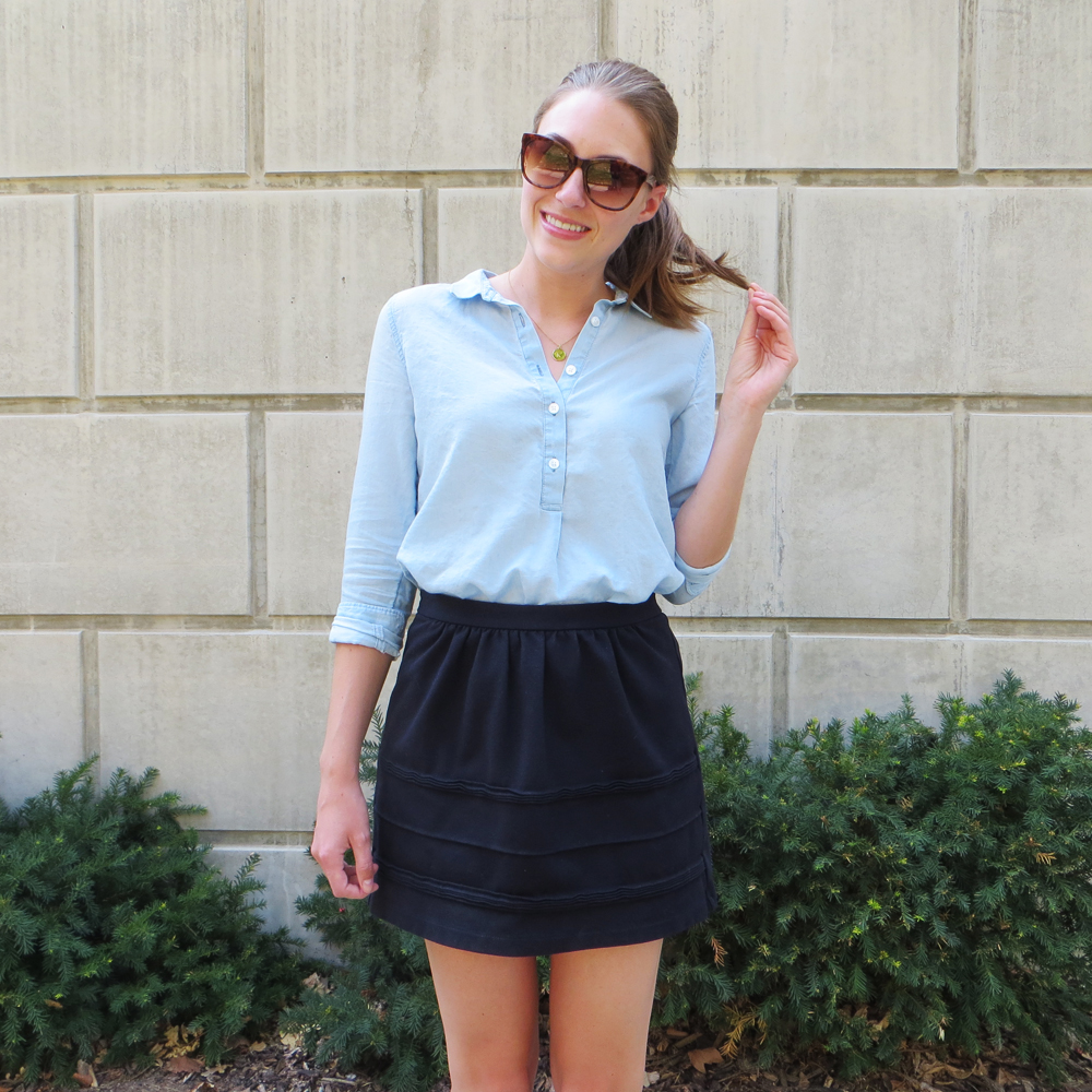 Light blue popover shirt, black mini skirt, monogram necklace -- Cotton Cashmere Cat Hair