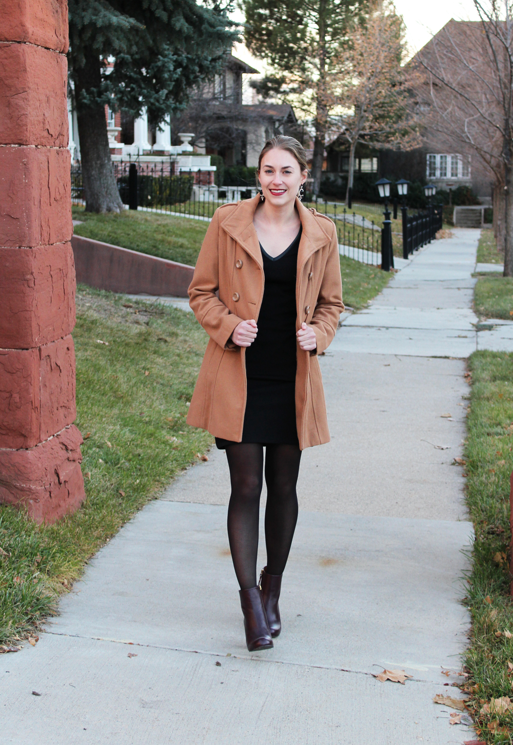 Camel coat, black dress, dark red ankle boots, statement earrings — Cotton Cashmere Cat Hair