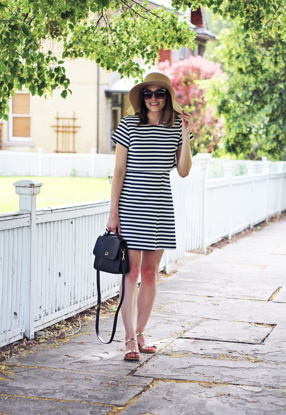 Navy striped dress, straw sun hat, navy Coach bag, gold sandals — Cotton Cashmere Cat Hair