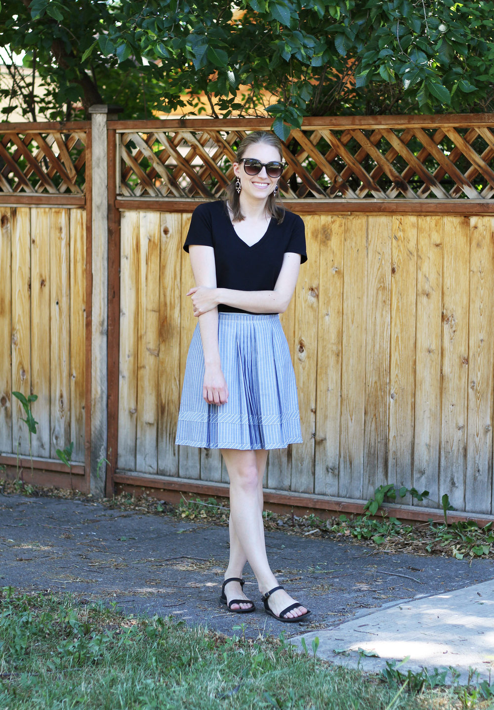 Black tee, blue Madewell shirtstripe skirt, black sandals, statement earrings — Cotton Cashmere Cat Hair
