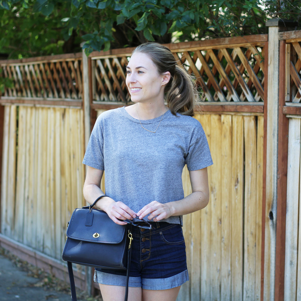 Grey cropped tee, high rise denim shorts, navy Coach 'Court' bag — Cotton Cashmere Cat Hair