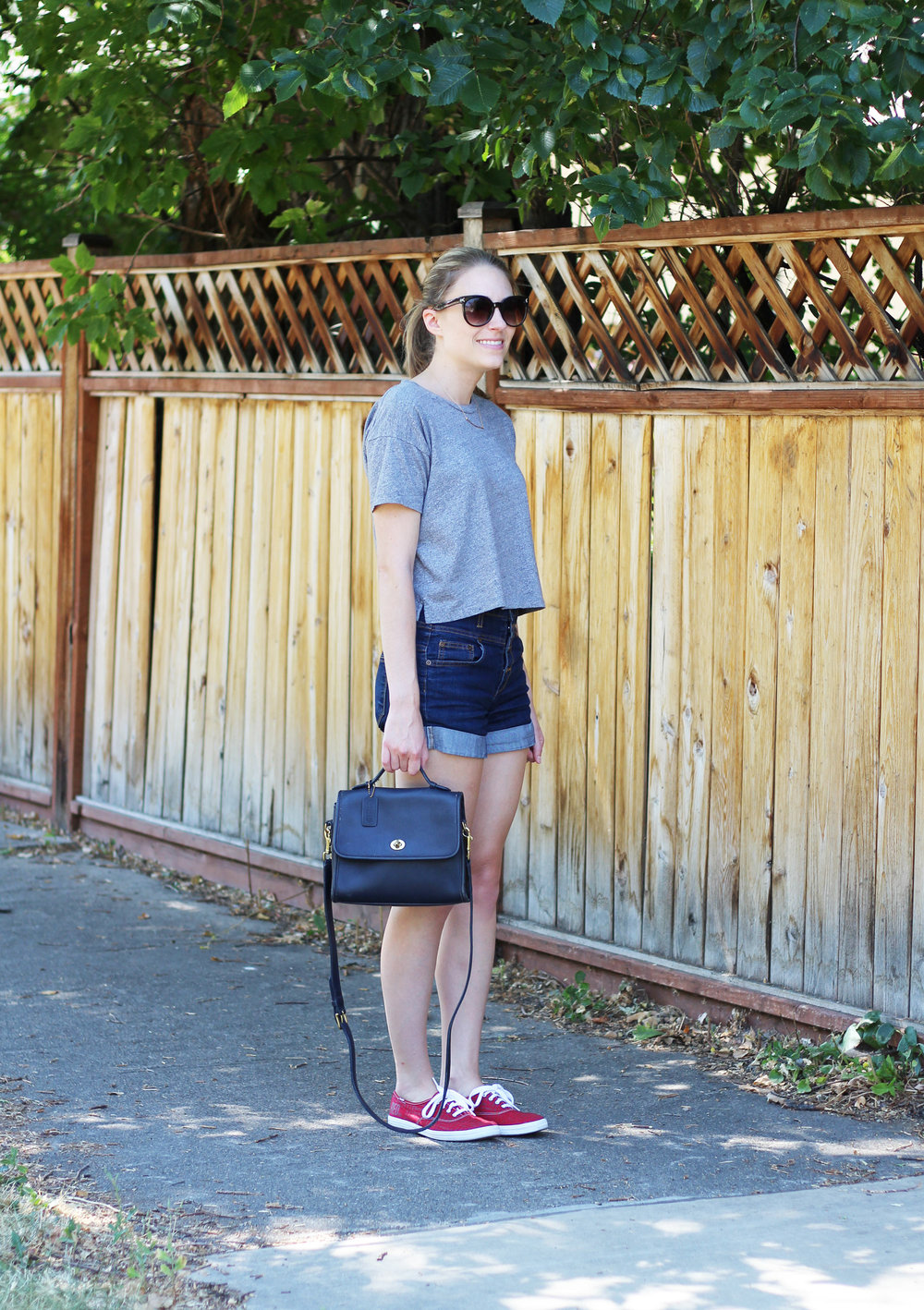 Grey cropped tee with high-rise denim shorts, red Keds, and navy vintage Coach bag — Cotton Cashmere Cat Hair
