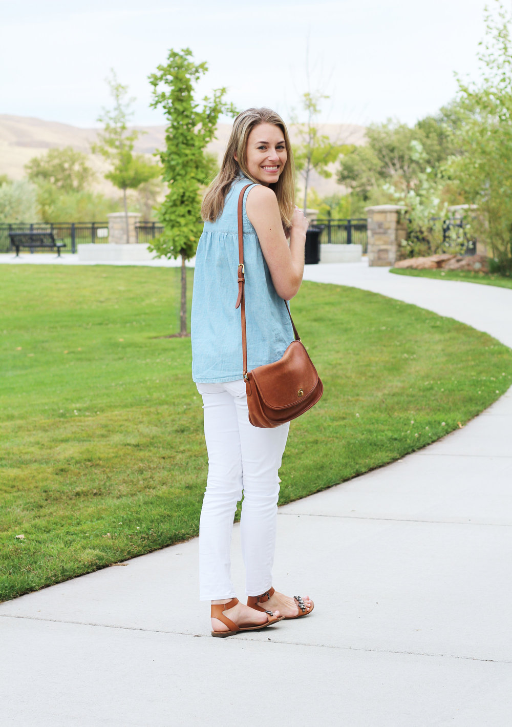 Sleeveless chambray shirt outfit with white jeans, cognac sandals, and Coach 'City' bag — Cotton Cashmere Cat Hair