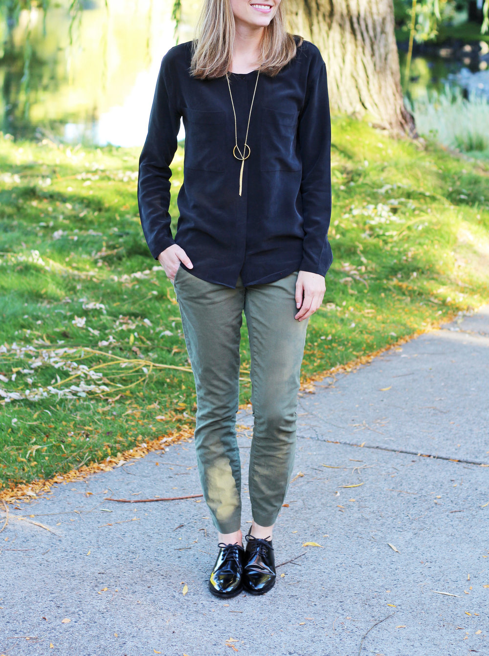 Black silk shirt, green chino pants, shiny black oxfords, pendant necklace — Cotton Cashmere Cat Hair