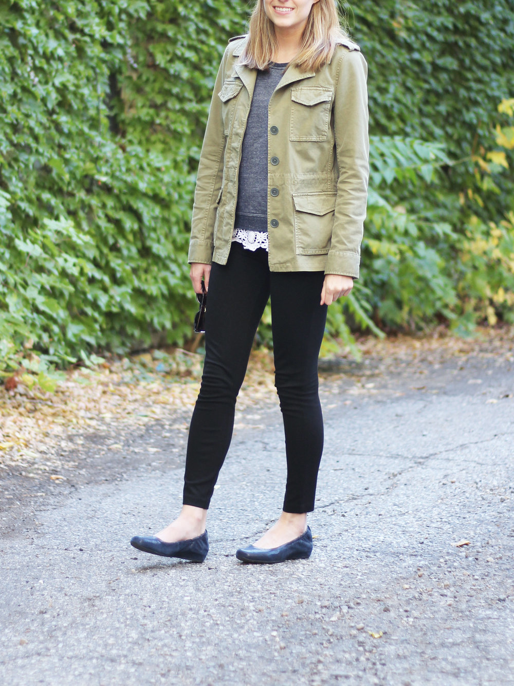 Green utility jacket outfit with navy sweater, lace top, black pants, navy flats — Cotton Cashmere Cat Hair