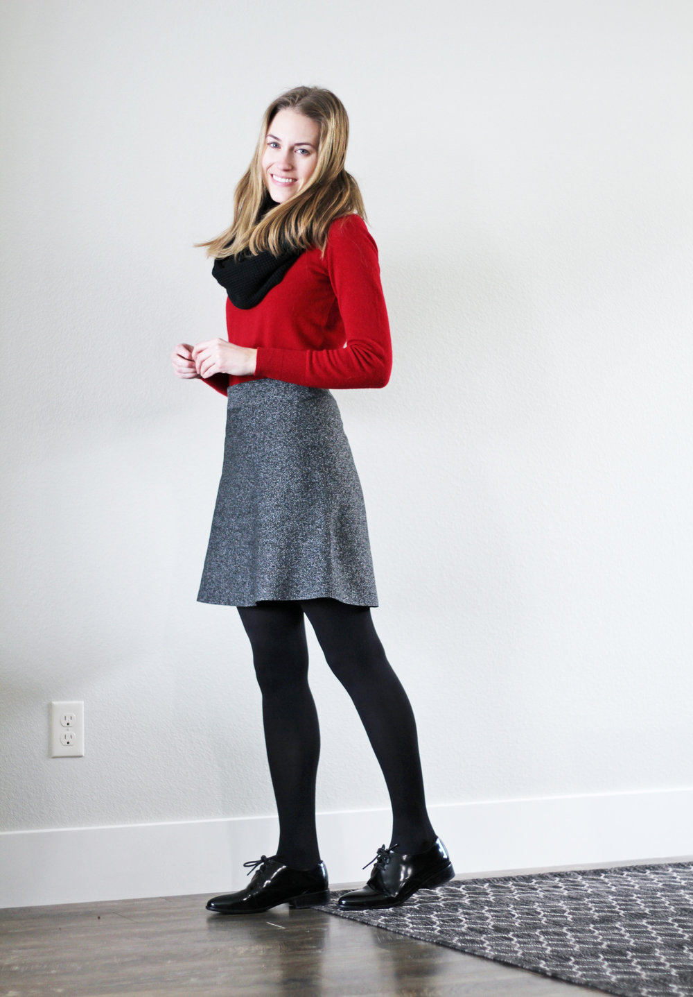 Red cashmere sweater outfit with black speckled skirt, shiny black oxfords, black scarf — Cotton Cashmere Cat Hair