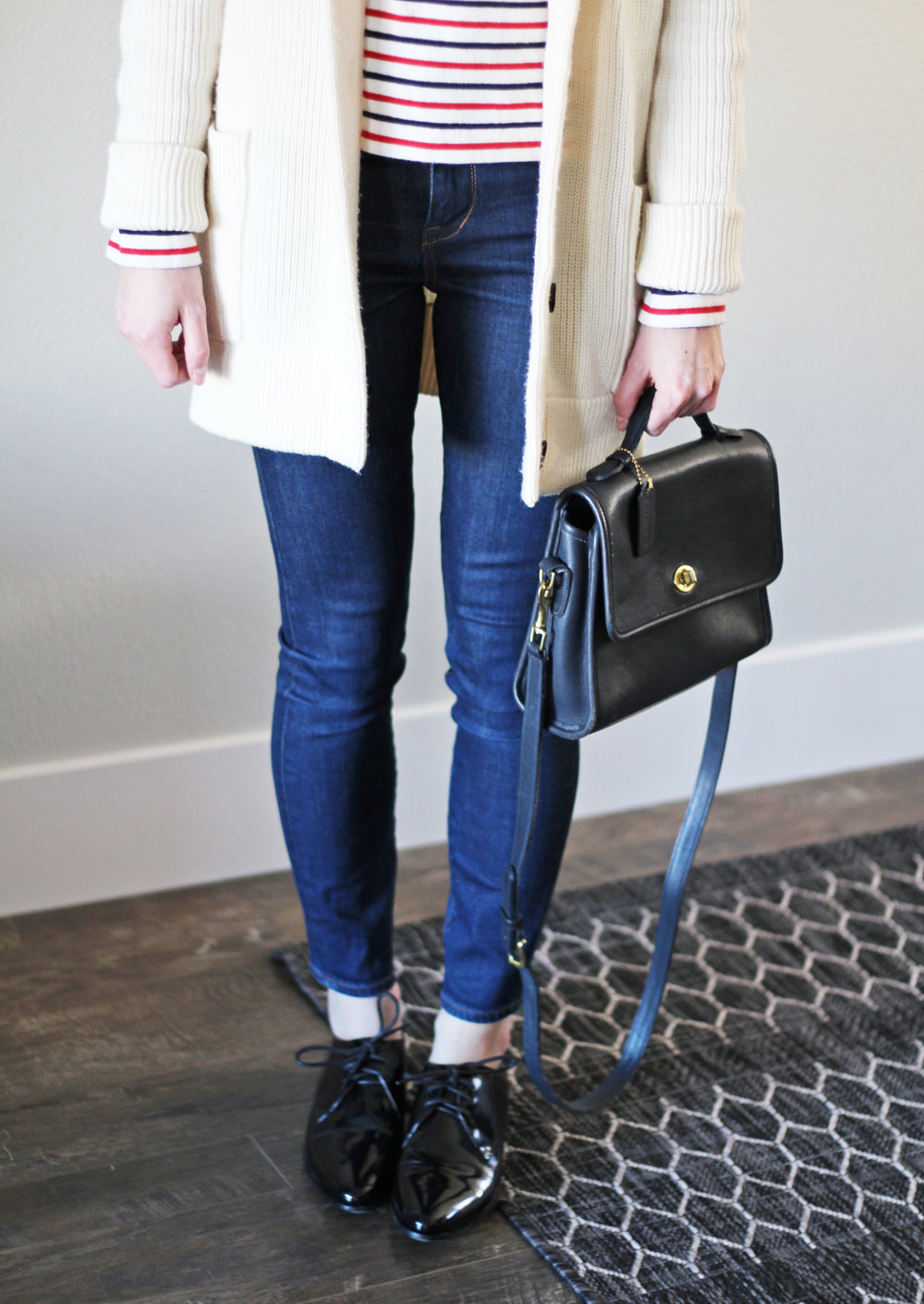 Navy Coach 'Court' bag outfit with ivory cardigan, striped tee, skinny jeans, shiny black oxfords — Cotton Cashmere Cat Hair