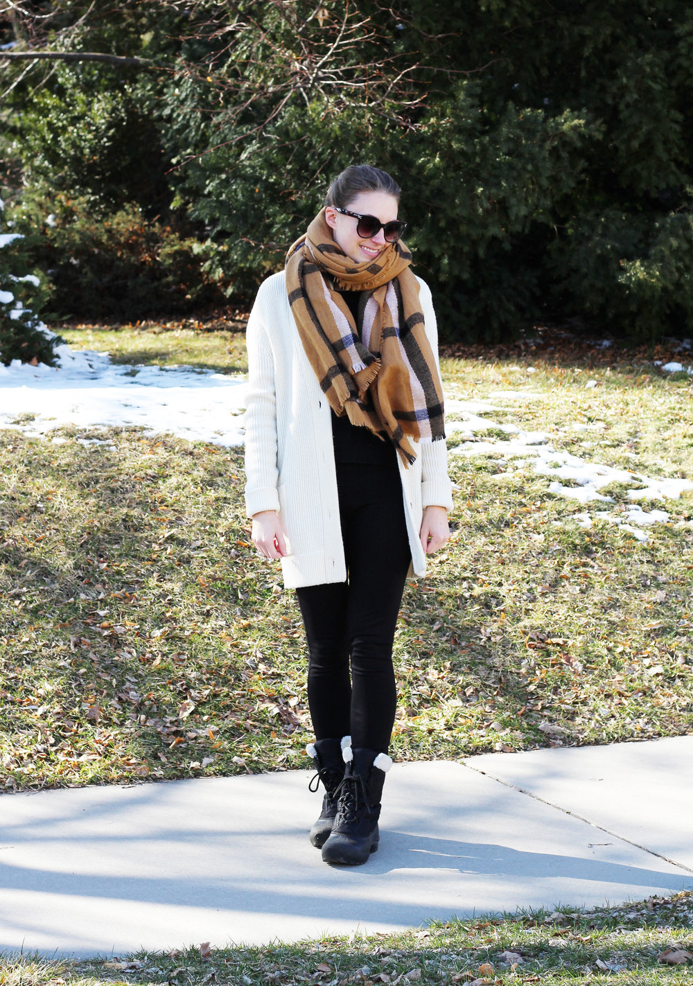 Cozy late winter outfit with camel blanket scarf, ivory chunky cardigan, and Sorel boots — Cotton Cashmere Cat Hair