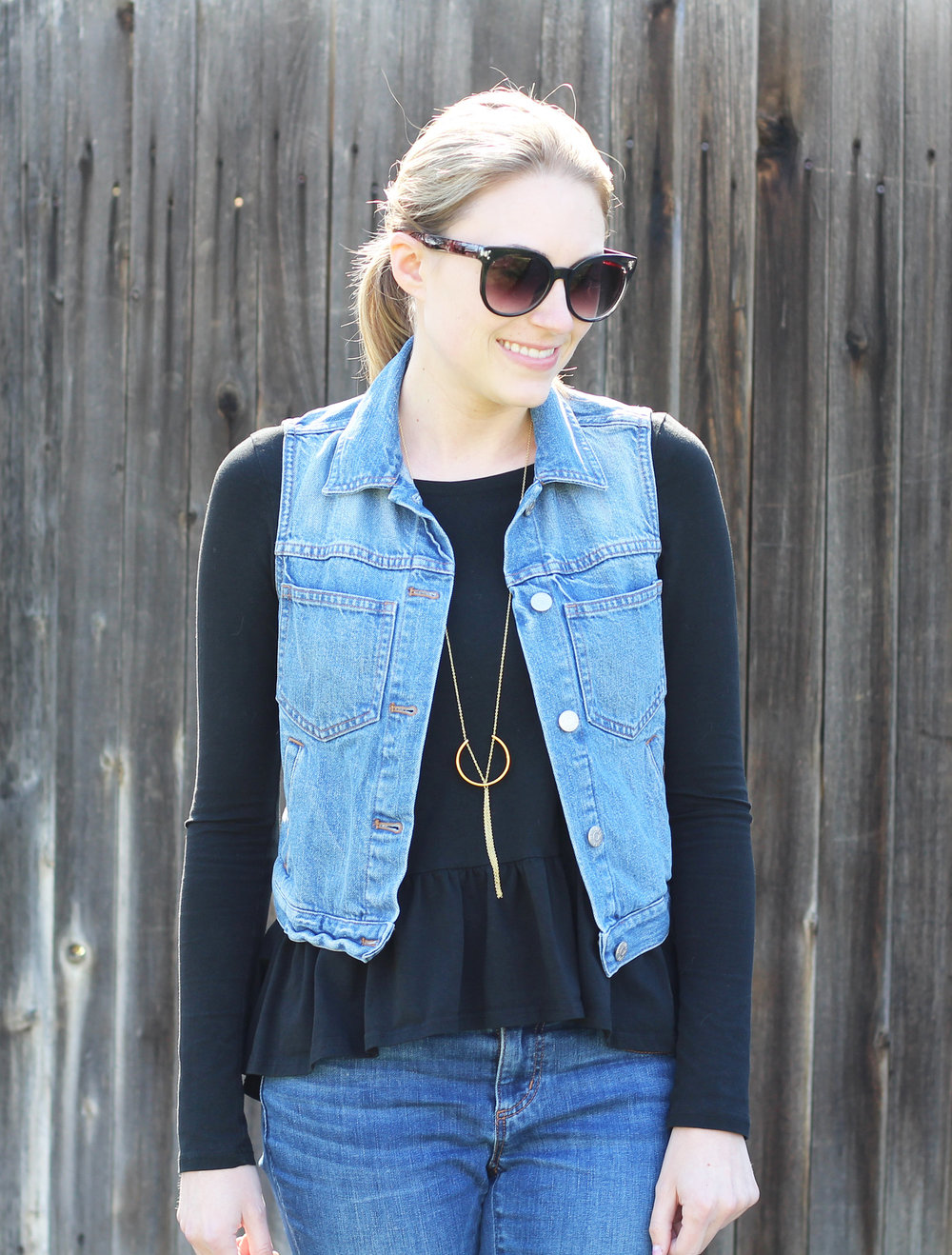 Denim vest outfit with black peplum top and pendant necklace — Cotton Cashmere Cat Hair