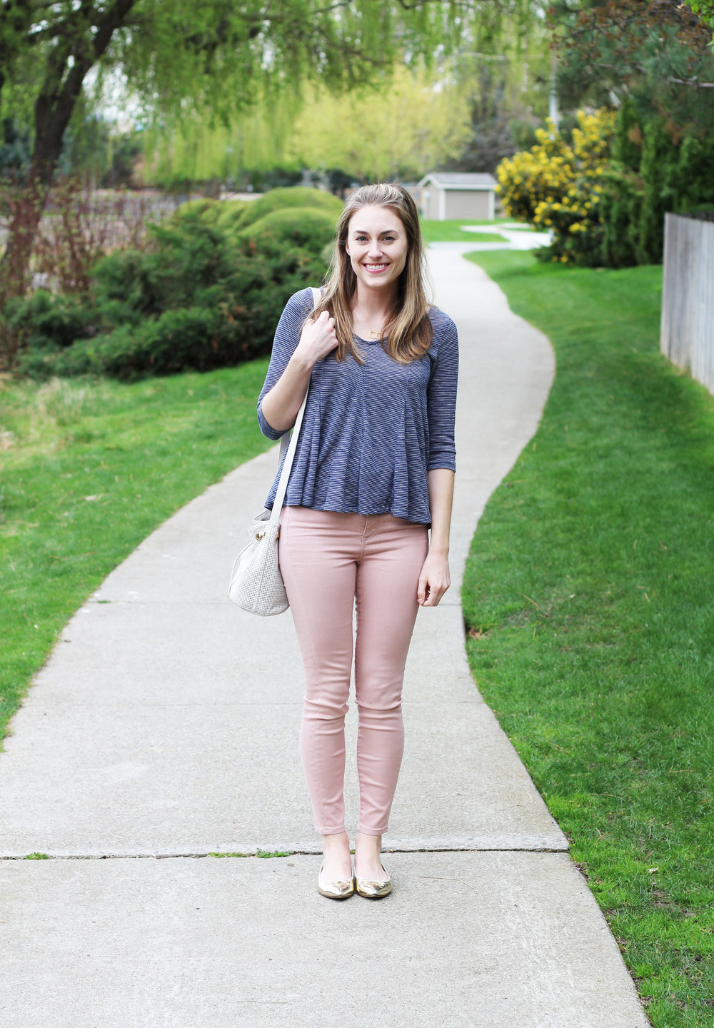 Blush pink skinny jeans outfit with navy swing top, gold flats, white bucket bag — Cotton Cashmere Cat Hair