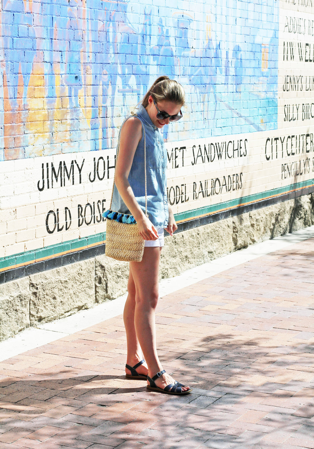 Blue tassel woven straw bag outfit with chambray shirt and navy sandals — Cotton Cashmere Cat Hair