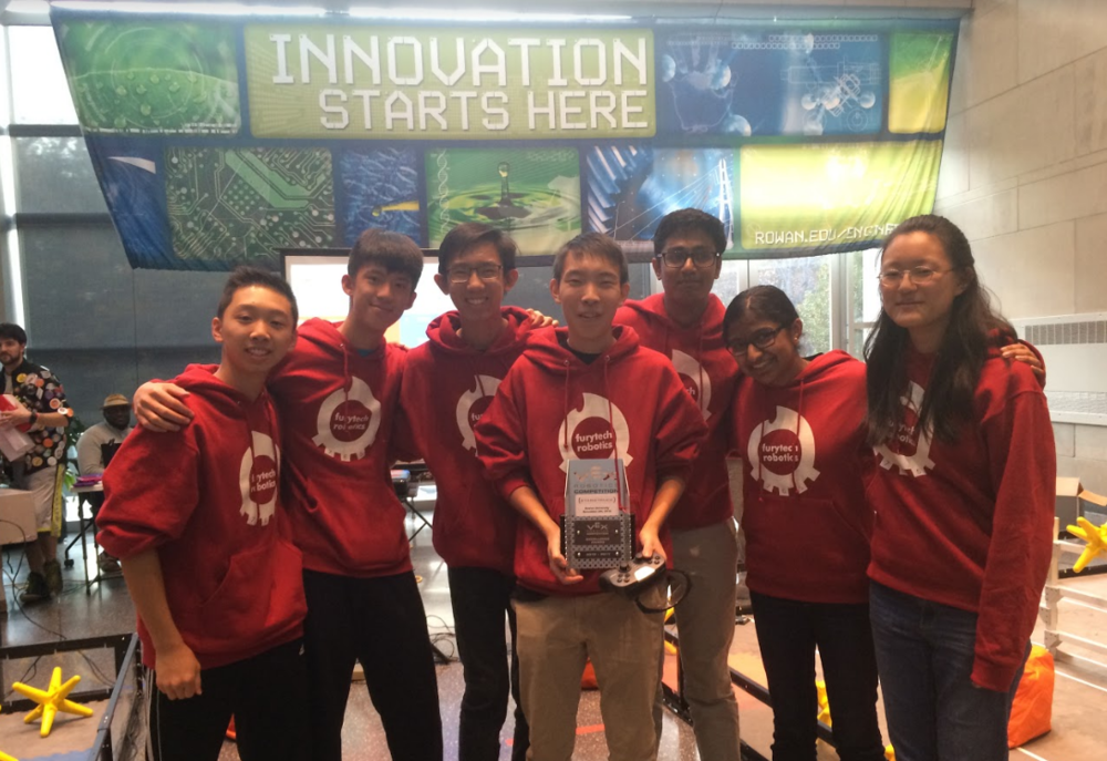 Team 765A is shown with their Excellence Award, which is presented to a team based on their quality of robot, skills score, design notebook, and their teamwork/collaboration.