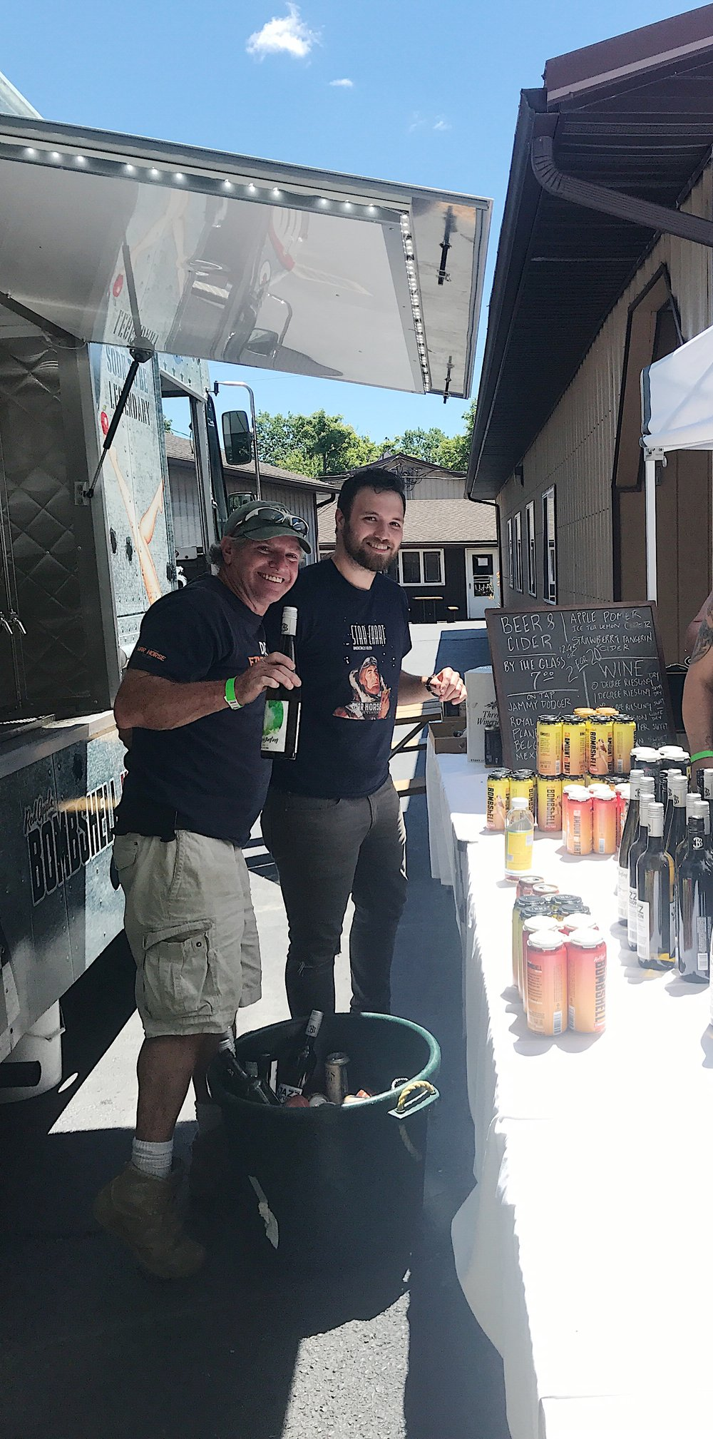Photo of owner Dave Mansfield and his son Jon Mansfield pouring wine and hard cider at the War Horse Brewery beer truck
