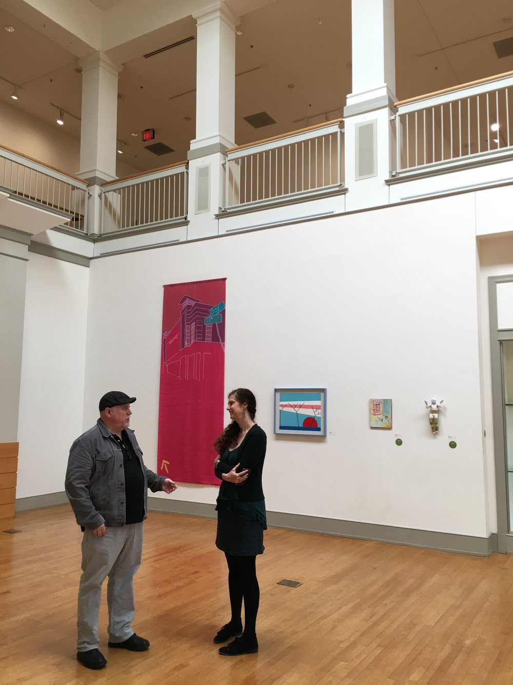 Beth Sale and Jon Biron discussing life and art at the Lyndon House Arts Center, Athens, GA USA.  We Are Here  hangs behind them