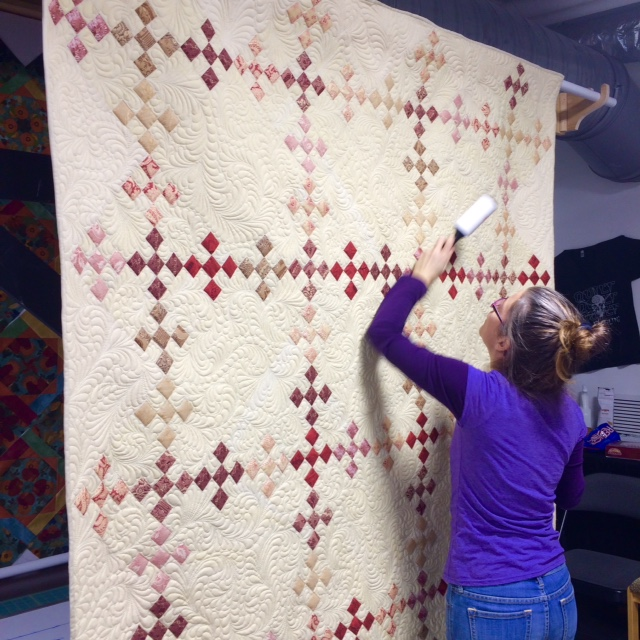 Editor Sara from OnWord Bound Books helps to remove any stray thread before photoshoot.   Quilt pieced by Ann Tash