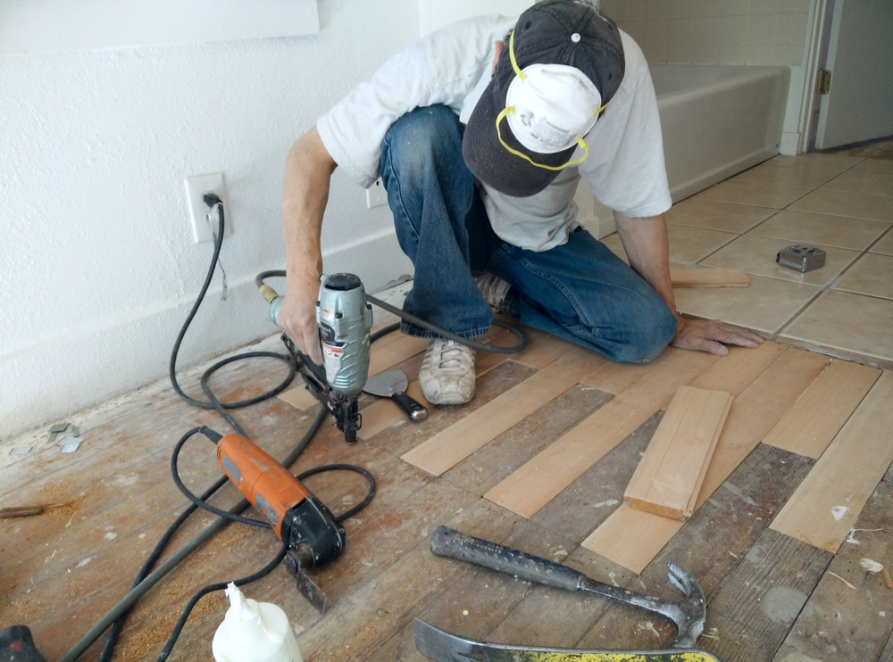 Nail-guns powered by compressed air are used to ensure floorboards are securely nailed down.
