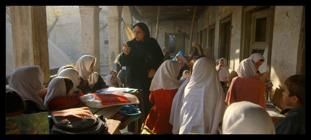 Film still: A classroom of girls at the original location of the Daqiqi Balkhi school, at the destroyed Gudri mosque
