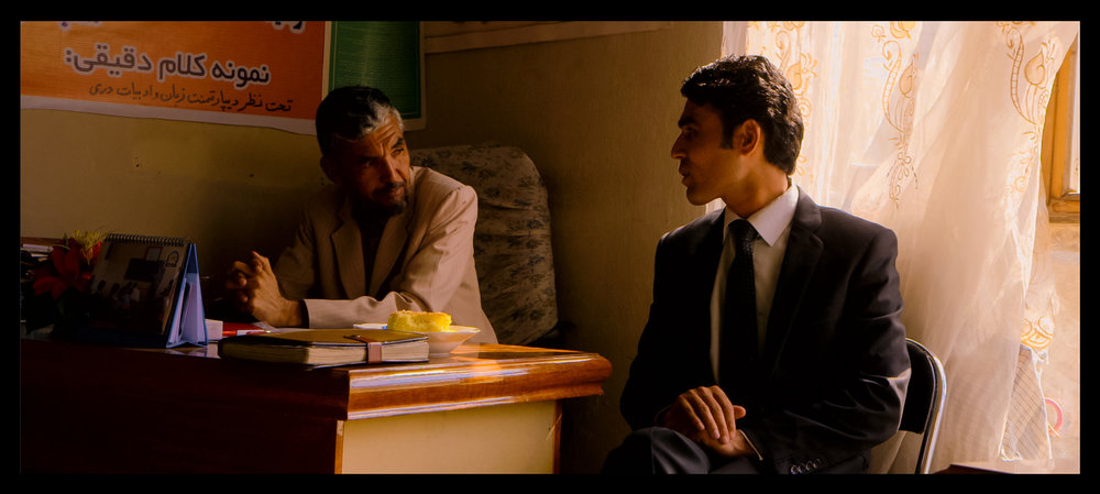 Film still: School principal Faiz Mohammed (left) speaks with a colleague at the Daqiqi Balkhi school