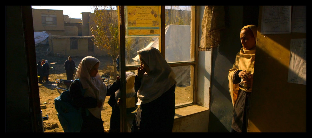 Film still: Gold and earthy color tones inside the office at the Daqiqi Balkhi school in Angels Are Made Of Light