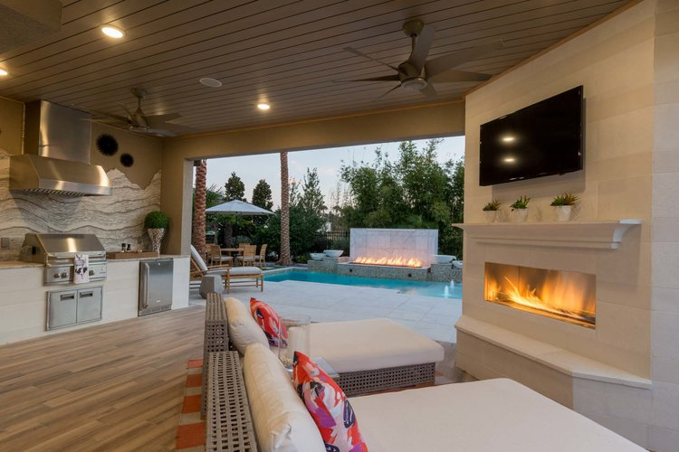 Boomer buyer model home patio with outdoor kitchen, pool and lounge seating
