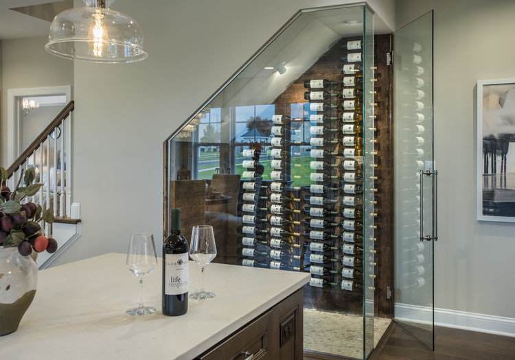 Creative floor plan with glass wine storage under stairwell in WB Homes.