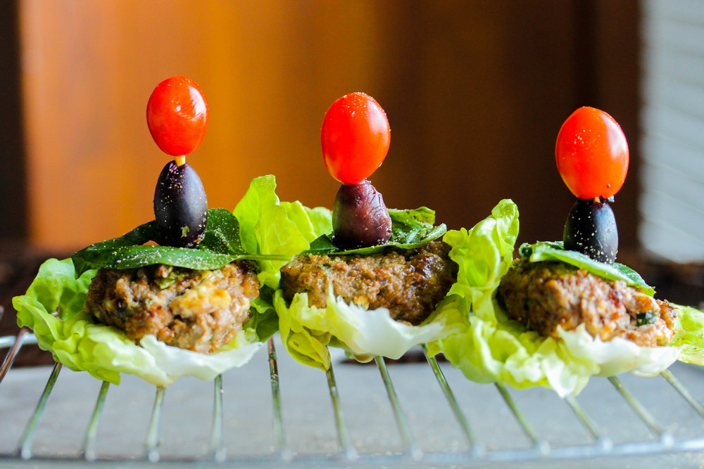 Assemble burgers on bib lettuce leaves and garnish with tomatoes and lives.