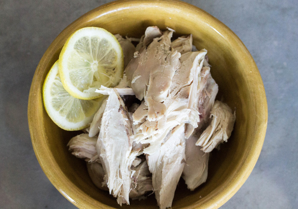 Once chicken is cooked (usually about 4 hours depending on slow cooker) take chicken off bone and set aside. Return skin and bones to slow cooker and let cook remaining time.