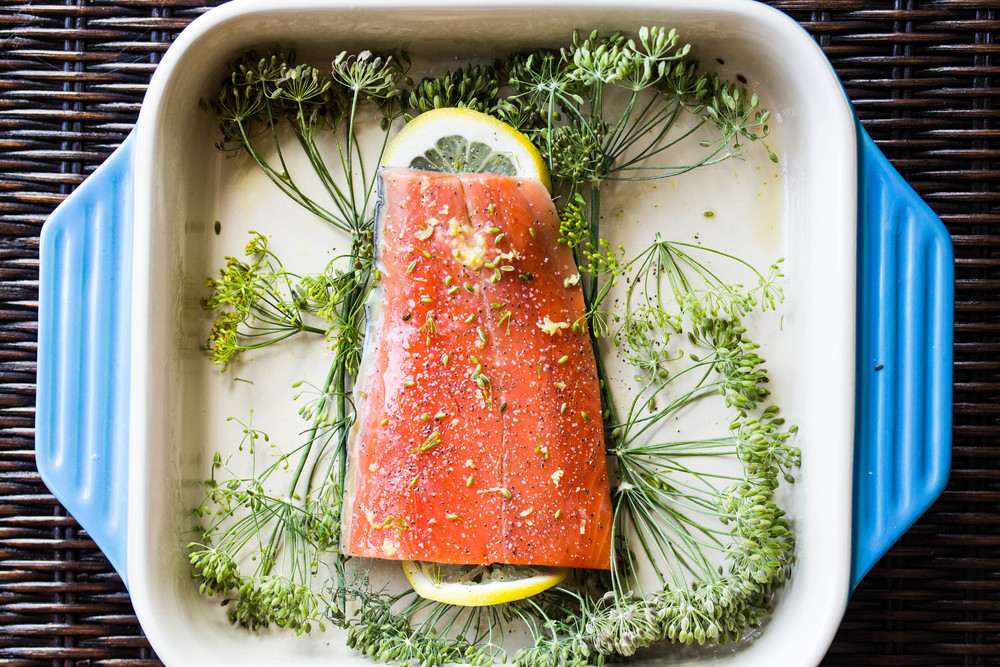 Place fish on top of herbs, brush with olive oil, and season with salt, pepper, and lemon zest.