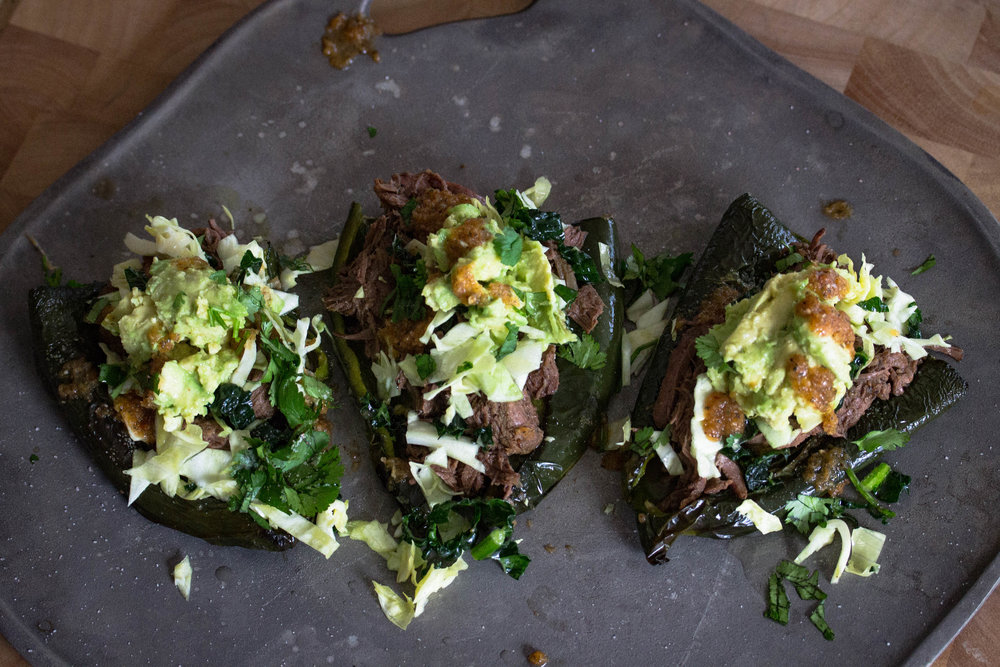 Serve barbacoa on top of roasted peppers topped with mashed avocado and shredded cabbage