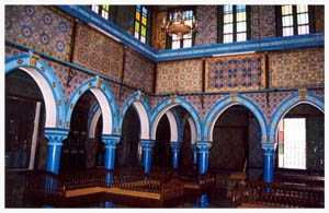 The many archways and ornate tiles adorning Djerba, Tunisia's fourteen synagogues evoke the flamboyant style of Muslim mosques more than they resemble traditional Jewish temples.