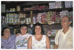"The Hamani family poses in their store in Obidos, on the Amazon River waterfront, where they have served passing navigators and ""caboclo"" jungle natives for decades. Mary (at far left) and Claudio (at far right) are first cousins. Marrying cousins was common among the Jewish communities of the Brazilian Amazon – where there were few other potential Jewish mates available. The Hamanis' daughters, Ester and Carolina, do not wish to marry their cousins – so they must leave the jungle interior or assimilate, marrying non-Jews. Claudio believes this factor will eventually doom the Jewish community in the Amazon interior. ""It is a great shame that the Amazon Jewish communities are disappearing,"" Claudio says, ""but our daughters don't want to marry their cousins, and there is virtually no one else."""