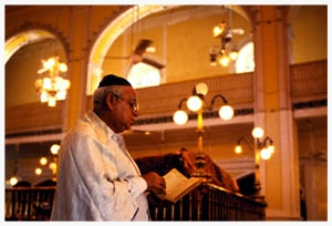 "Ben Zion Gosalkar, the Bene Israel caretaker (Shamash) of massive Knesseth Eliyahoo synagogue in Bombay, prays during the afternoon service (Mincha). The 19th century temple once housed India's wealthy Baghdadi Jewish community, but today the prayer leader (Chazzan) and most congregants are Bene Israel. Ben Zion has tears in his eyes before the service remembering his synagogue 50 years ago, before the vast majority of India's Jews emigrated to Israel. ""There were 15,000 Jews in Bombay – people would sleep next door to walk to synagogue on holidays. We needed extra services in the Sassoon Library across the street because there wasn't room for everyone."" Scanning nostalgically from the rows of empty benches to the unused women's gallery, he sighs, ""Today, even on Yom Kippur there are only 25 people."""