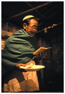 "Rachamim Hanshing, in traditional Benei Menashe shawl, prays over the staple food, rice, at a crowded dinner for Jewish family and friends. In his spare time, Rachamim, a metalworker, handicrafts mezuzot (small boxes containing prayers, attached in doorways and gates of Jewish homes). Rachamim's father was a great tiger and elephant hunter in the hills around Imphal, the capital of Manipur, in northeastern India. Today, Rachamim says, ""We are waiting for the land of Menasseh in Israel."""