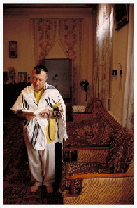 "Every morning, Rafael Davydov, the former President of the Bukharian Jewish community, wears tefillin as he rapidly recites the shacharit service in Hebrew, barefoot in his bedroom. ""I only started to teach myself Hebrew…after I became the community President,"" Rafael confides. During the Soviet era, it was prohibited and impossible. ""In spite of the fact that I didn't know Hebrew,"" Raphael says, ""we always ate kosher food, fasted on Yom Kippur, observed Pesach, and quietly performed circumcisions and bar mitzvahs."" Now the community has religious freedom, but the Jews are leaving en masse. ""It's too bad all the Jewish people left to America, Israel, Germany -- before we all lived here together as neighbors,"" Raphael laments."