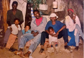 A picture of our house in Nairobi. On the left is my step dad my brother leaning on him and am next at the age of 2yrs. The rest are just friends.