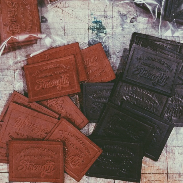 Hand-made leather labels after the dying process. Photo by Rick Bloomer