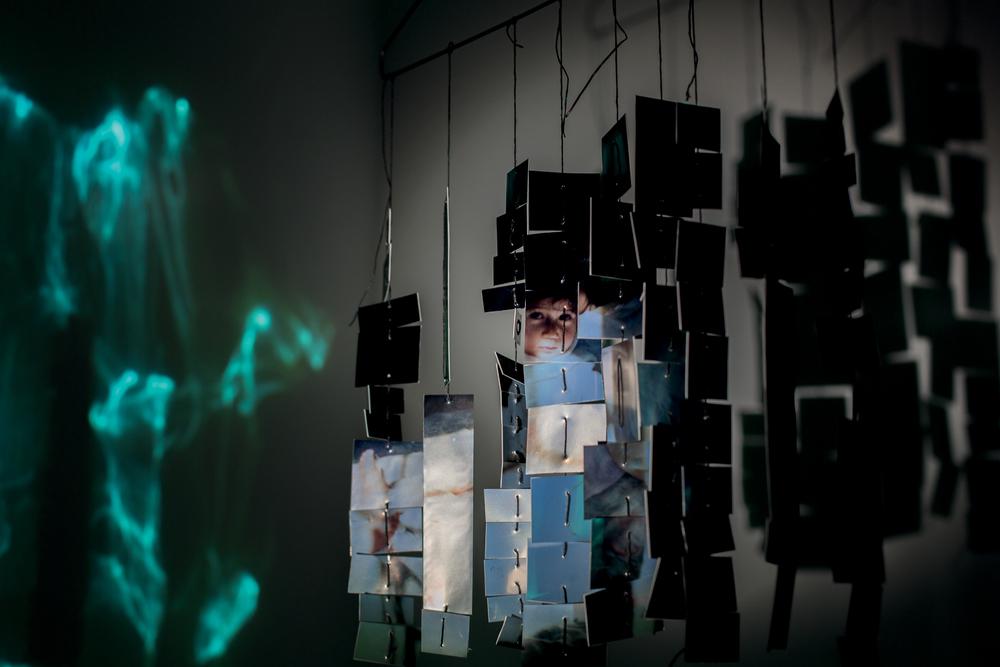 Archival pigment print on aluminium, string, hanger, lamp, mylar reflection, fan.