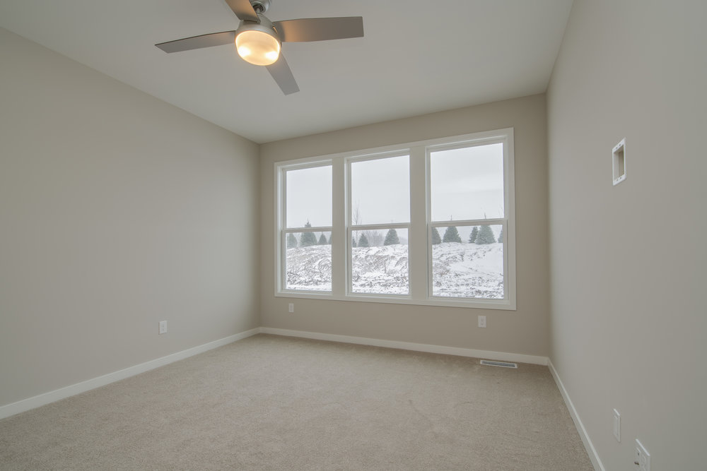 Main-floor owner's suite features a ceiling fan