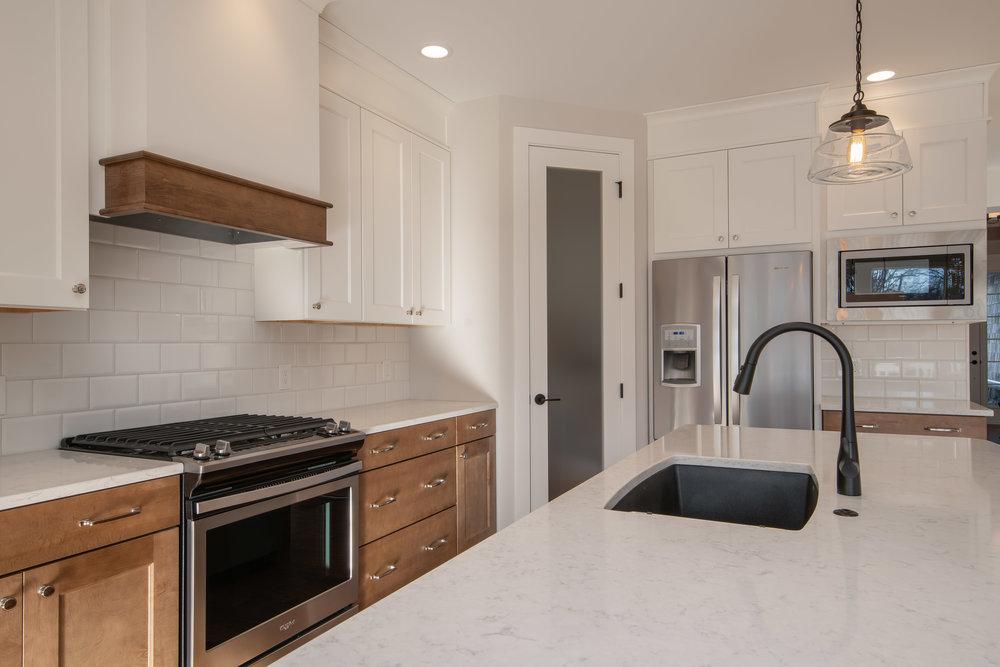 Stainless steel appliances, custom range hood, large pantry and modern lighting