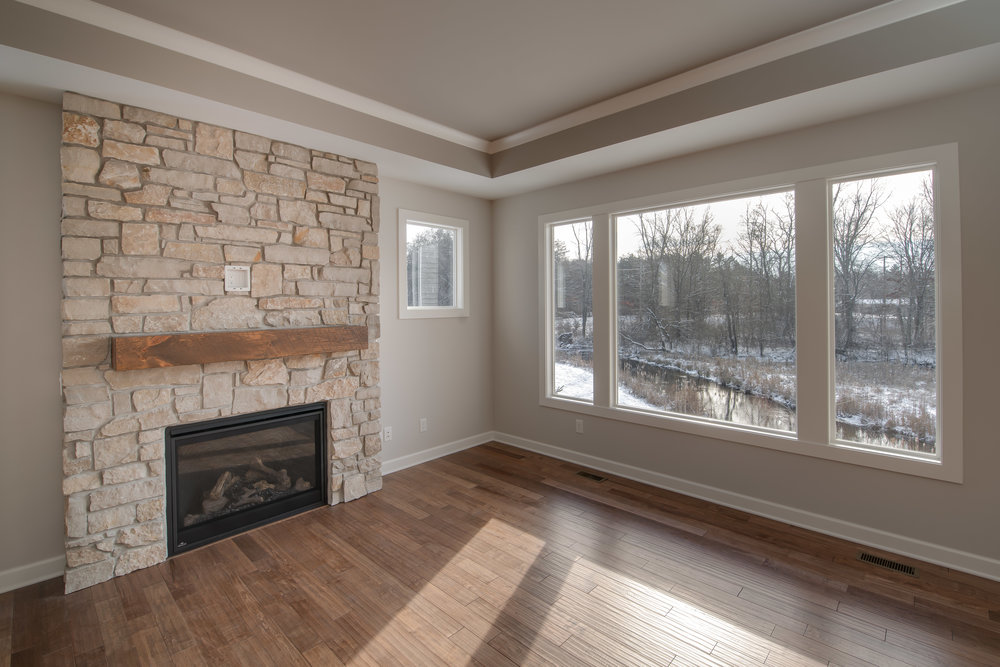 Fireplace with stone surround and custom wood mantel