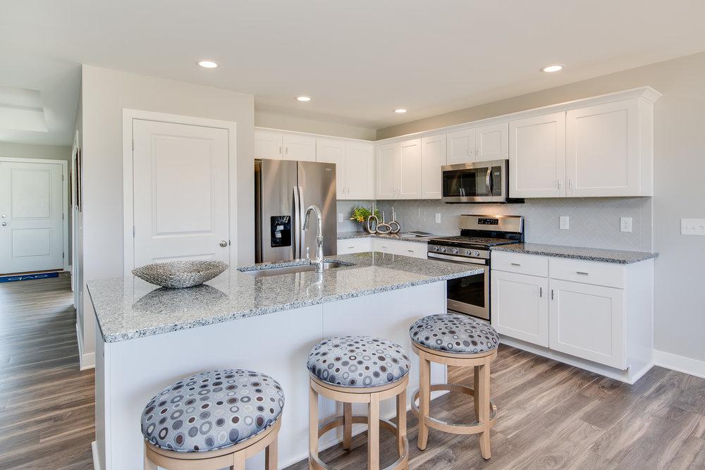 5 1 2018 AC-01-28-Bluebell_Kitchen_White Cabinets_Granite_LVP_Stainless.JPG