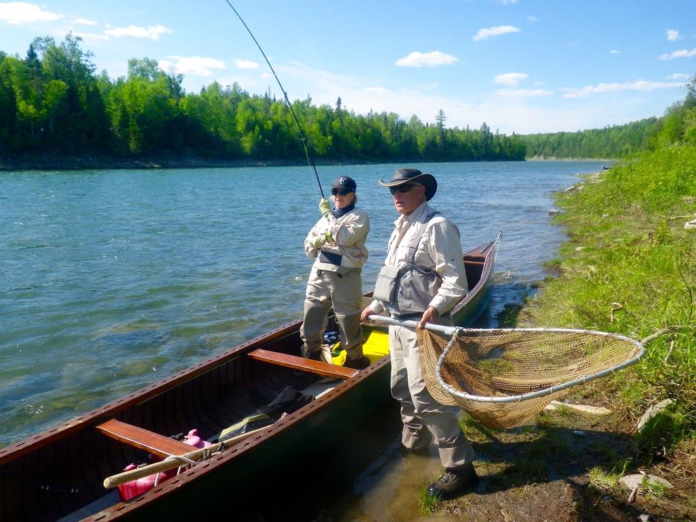 Sylvie Lalande est en train de capturer un saumon sous l'œil attentif du guide du Camp Bonaventure, Jean-Marc Poirier. En 2016, c'est la 52eannée que Jean-Marc passe sur la rivière! Nos félicitations à Sylvie et, bien sûr, à Jean-Marc.