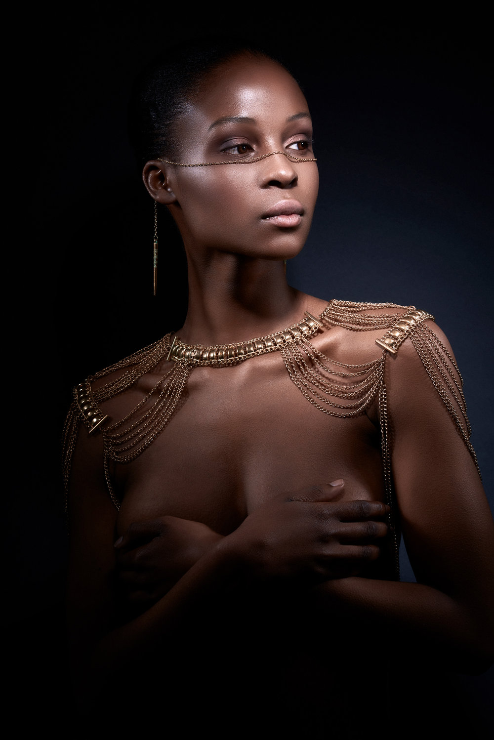 moody lighting nude model wearing face and body chain jewellery fashion photography