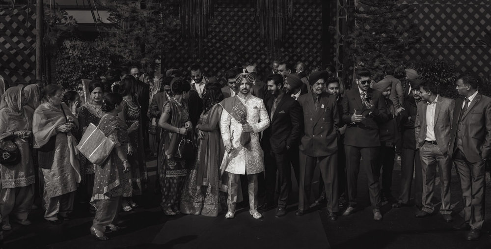indian groom posing whilst everyone around him talking to each other happily wedding photography