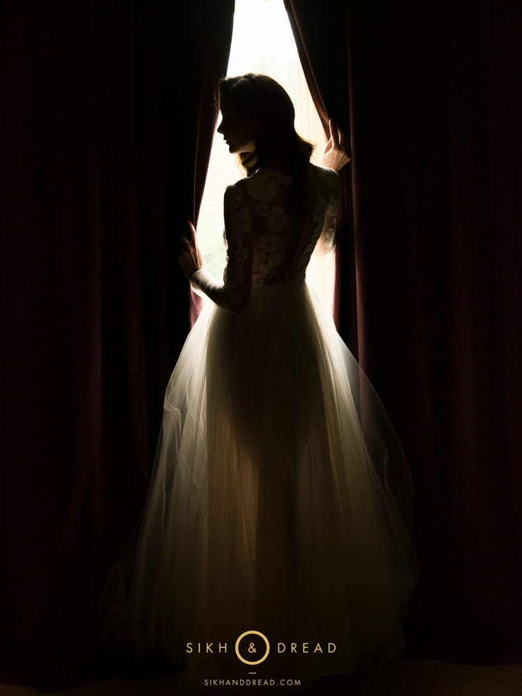bride standing in front window with curtains parted with her hands Best Asian Wedding Photographers London