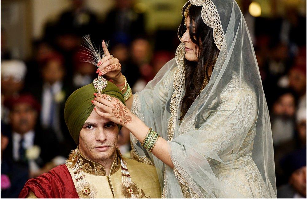 Sister of Sikh groom adjusting his turban