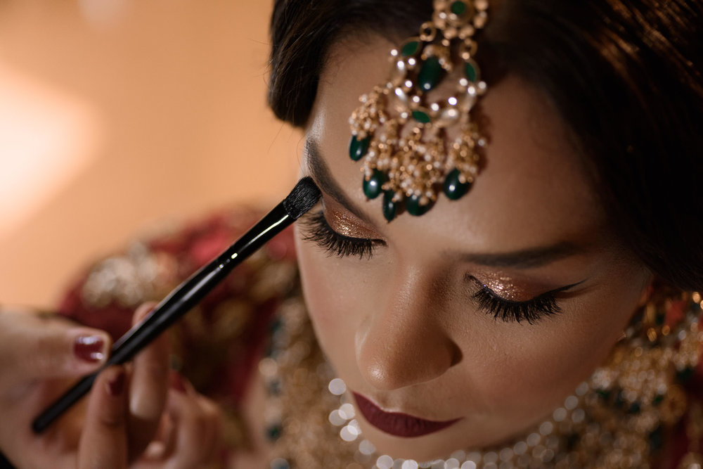 Sikh bride getting ready having makeup applied