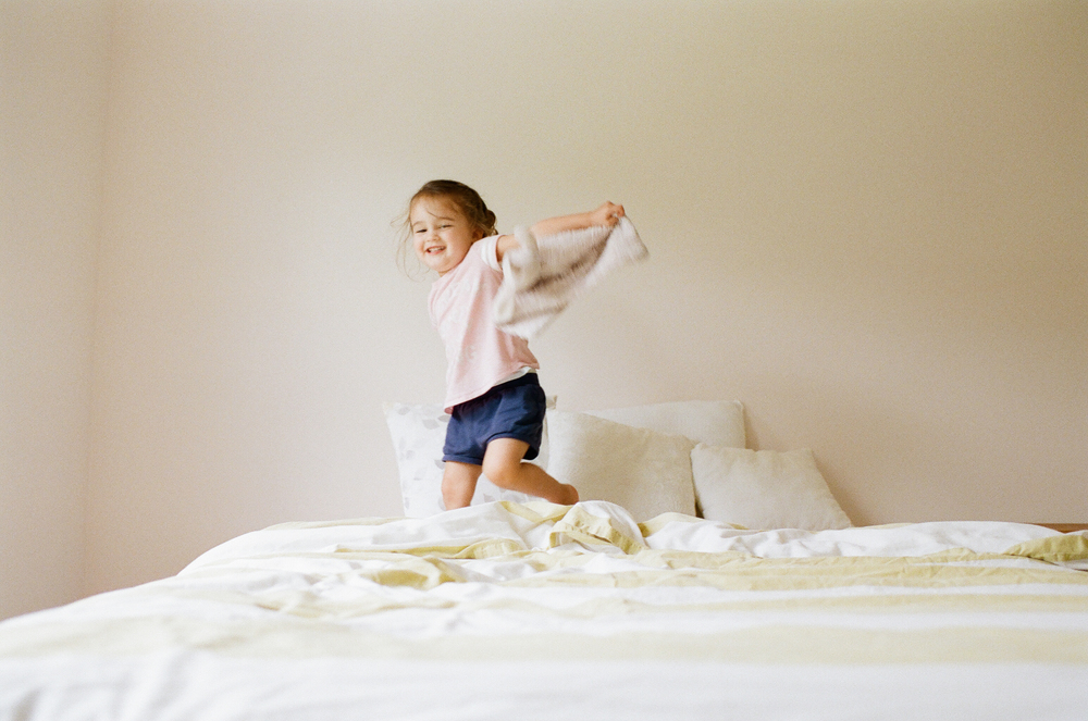 little girl jumping on bed | DC family and film photographer | Yasmina Cowan Photography