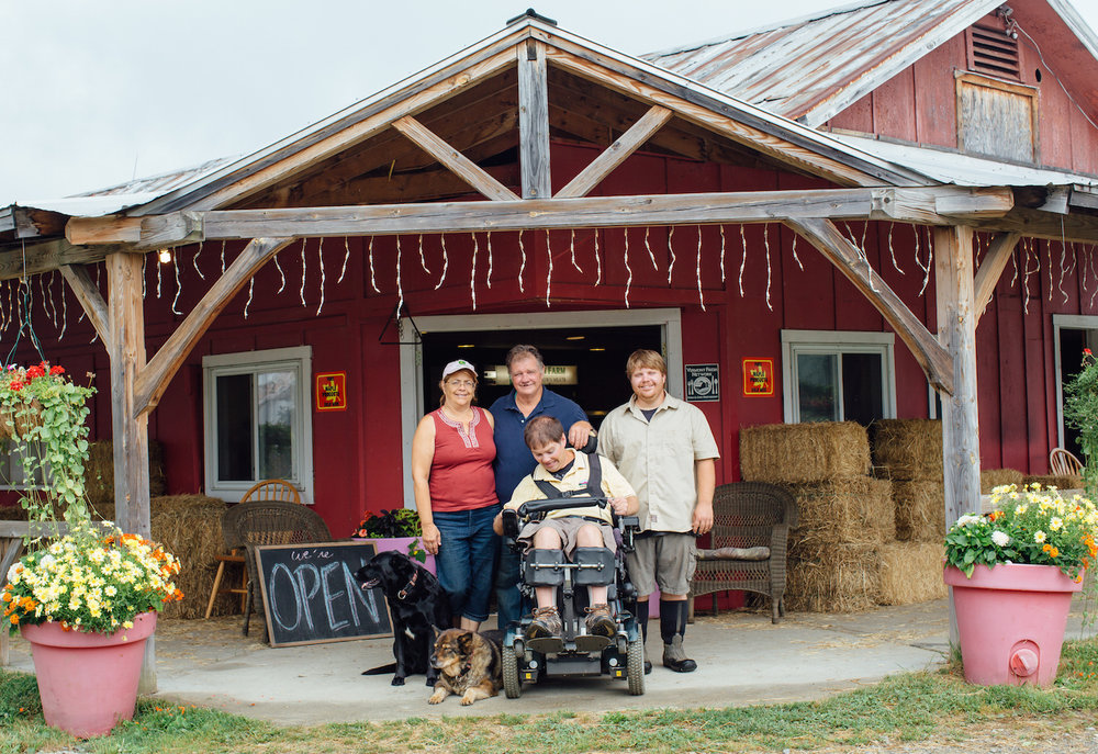 The Tisbert Family, Anne, Joe, Jay, and John, in front of their farm stand