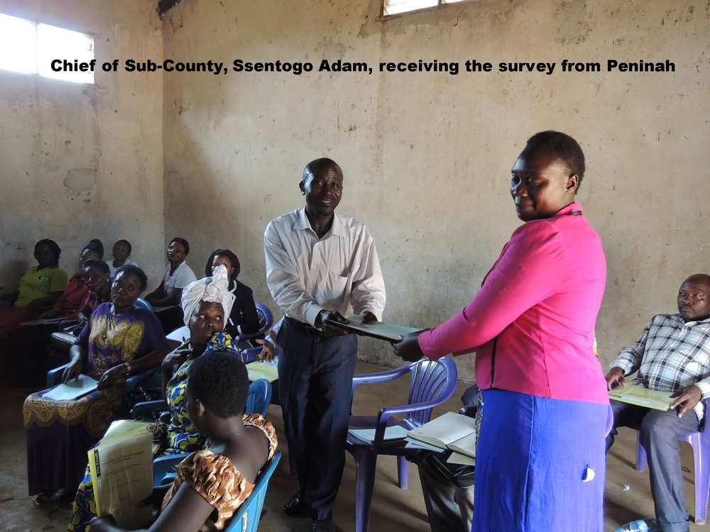 Peninah presenting the survey to the Sub-County chief, Ssentongo Adam.